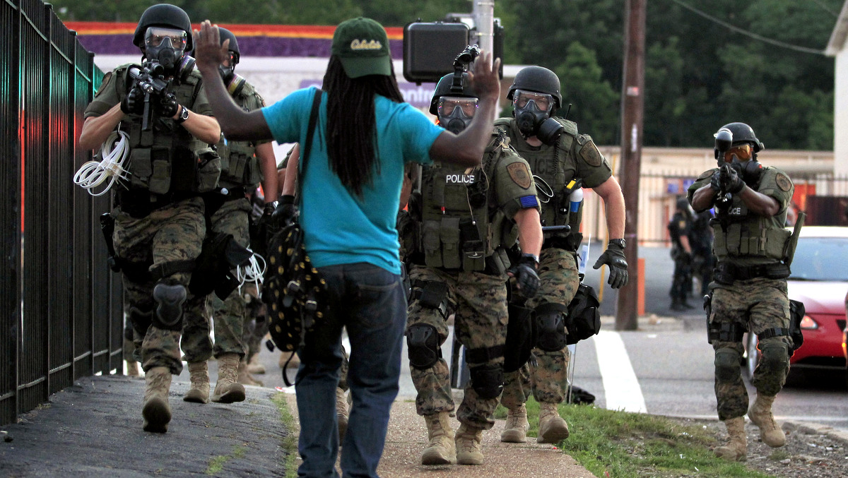 Police wearing riot gear walk toward a man with his hands raised Monday, Aug. 11, 2014, in Ferguson, Mo. (Photo/Jeff Roberson,AP)