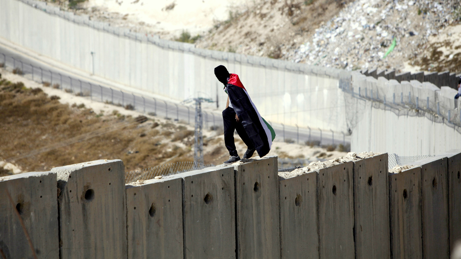 A student wrapped in a Palestinian flag walks over Israel's apartheid wall between the West Bank and Israel in Abu Dis during a protest Monday, Nov. 2, 2015. (AP Photo/Mahmoud Illean)