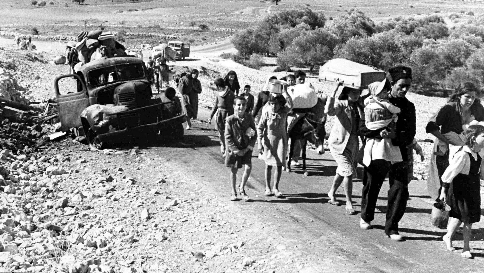 A group of struggling Arab refugees walk along the dusty road from Jerusalem to Lebanon, carrying their meager belongings with them, Nov. 9, 1948. The Arabs have been driven from their homes by Jewish attacks in Galilee. (AP/Pringle)