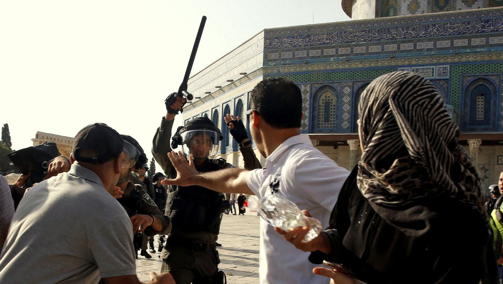An Israeli police officer raises his baton on Palestinians worshipers near the Al Aqsa Mosque in Jerusalem's Old City, July 27, 2017 (AP/Mahmoud Illean)